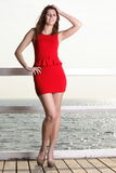 Young woman in red dress on the pier Royalty Free Stock Image