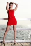 Young woman in red dress on the pier Royalty Free Stock Images