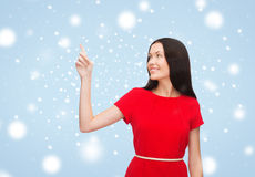 Young woman in red dress pointing her finger Stock Photo