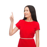 Young woman in red dress pointing her finger Royalty Free Stock Image