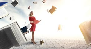 Young woman reading a book. Mixed media. Young woman in a red dress reading a book with other books flying around. Mixed media royalty free stock images