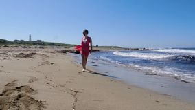 Young woman in red dress running on the sandy beach enjoying the sun and posing. Water splashing and wind blowing. Slow motion stock video