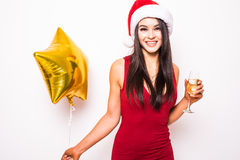 Young woman in red dress and santa christmas hat with gold star shaped balloon smiling and drinking champagne Stock Photos