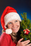 Young woman in red dress and Santa hat on blue dark background. Smiling holding a small Christmas tree with one red ball decoratio Stock Image