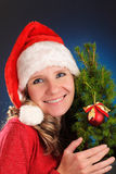 Young woman in red dress and Santa hat on blue dark background. Smiling and looking at camera. Holding a small Christmas tree with Stock Photography