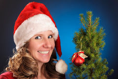 Young woman in red dress and Santa hat on blue dark background. Smiling and looking at camera. Holding a small Christmas tree with Royalty Free Stock Image