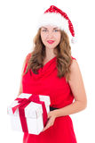 Young woman in red dress and santa hat with christmas present is Stock Images