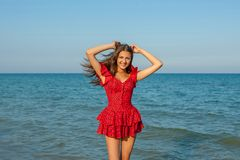 Young woman in red dress on the sea Royalty Free Stock Images