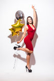 Young woman in red dress with shaped balloon Stock Photo