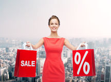 Young woman in red dress with shopping bags Stock Images