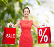Young woman in red dress with shopping bags Royalty Free Stock Images