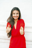 Young woman in red dress showing thumb up Royalty Free Stock Images