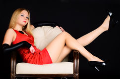 Young woman in red dress sitting in chair. Stock Photo