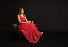 Young woman in red dress sitting on a chair Royalty Free Stock Images