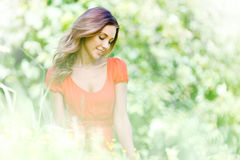Young woman in red dress sitting on grass Stock Photos