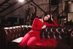 Young woman in red dress sitting on leather sofa Stock Photos
