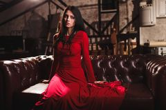 Young woman in red dress sitting on leather sofa. Elegant sensual young brunette woman in red dress sitting on leather sofa Royalty Free Stock Photography