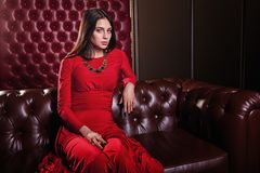 Young woman in red dress sitting on leather sofa Stock Image