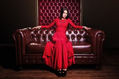 Young woman in red dress sitting on leather sofa Royalty Free Stock Photo