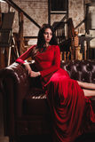 Young woman in red dress sitting on leather sofa Royalty Free Stock Image