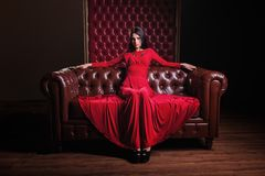 Young woman in red dress sitting on leather sofa Stock Images