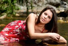 Young woman in red dress sitting in river water in summer Royalty Free Stock Photo
