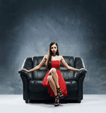 A young woman in a red dress sitting on a sofa Royalty Free Stock Photo