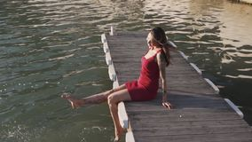 Woman in dress sitting on wooden pier, swings her feet in water, slow motion. Young woman in red dress sitting on wooden pier, swings her feet in water, slow stock video footage