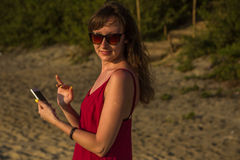 Young woman in red dress with smartphone on the beach Royalty Free Stock Images