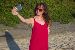 Young woman in red dress with smartphone on the beach Stock Image