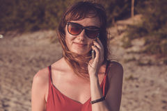 Young woman in red dress with smartphone on the beach Royalty Free Stock Photography