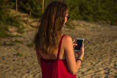 Young woman in red dress with smartphone on the beach Royalty Free Stock Image