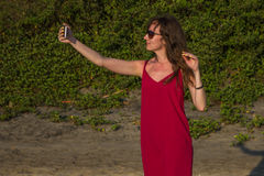 Young woman in red dress with smartphone on the beach Stock Photography