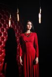 Young woman in red dress standing near wall Stock Images