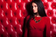 Young woman in red dress standing near wall Royalty Free Stock Photography