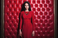 Young woman in red dress standing near wall Royalty Free Stock Images