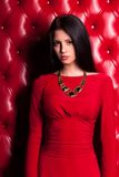 Young woman in red dress standing near wall Stock Image
