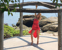 Young woman in red dress standing on tiptoe inside round alcove on sunny day with seaview at background Royalty Free Stock Photos