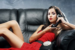 A young woman in a red dress talking on the phone Stock Photos