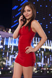 Young woman in a red dress talks on the phone while out in the c Royalty Free Stock Photos