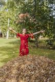 Young woman in red dress. Toss the autumn leaves upward. royalty free stock images