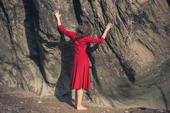 Young woman in red dress touching rock Royalty Free Stock Photography