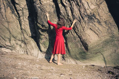 Young woman in red dress touching rocks Stock Photography