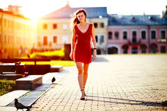 Young woman in red dress walking in city looking at camera. Royalty Free Stock Image