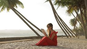 Young woman in a red dress walking by the sea. She is using a tablet and smiling. Beautiful brunette in a red long dress and sunglasses walking by the sea. The stock video footage