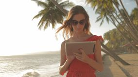 Young woman in a red dress walking by the sea. She is using a tablet and smiling. Beautiful brunette in a red long dress and sunglasses walking by the sea. The stock video
