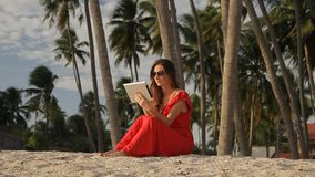 Young woman in a red dress walking by the sea. She is using a tablet and smiling. Beautiful brunette in a red long dress and sunglasses walking by the sea. The stock footage