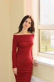 Young woman in red dress by the window Royalty Free Stock Image