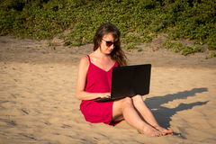 Young woman in red dress is working on laptop on the beach. Free Royalty Free Stock Photo