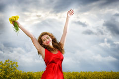 Young  woman in red dress in yellow field Stock Photos
